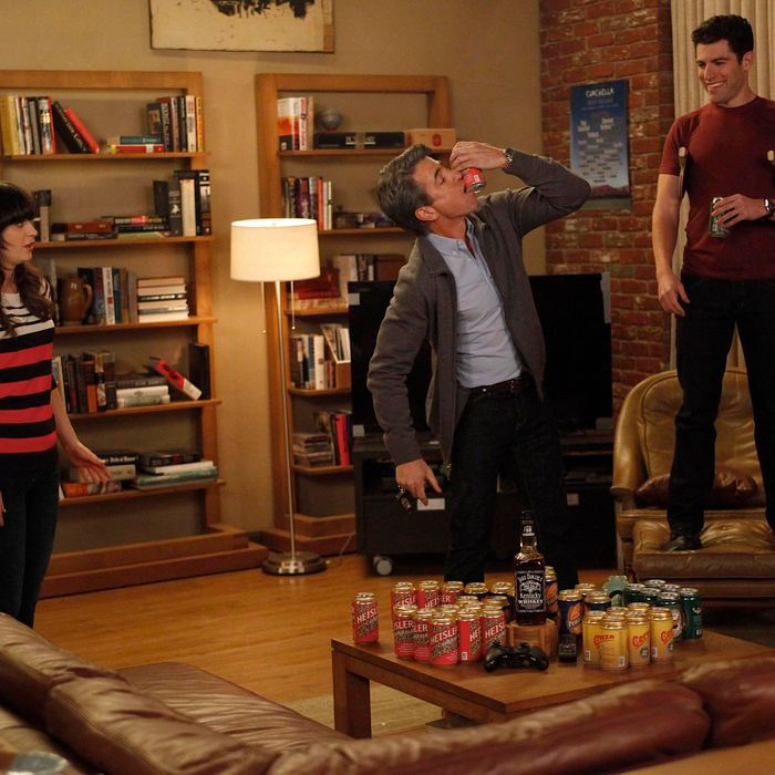 The gang plays drinking games when Jess (Zooey Deschanel, L) invites Russell (guest star Dermot Mulroney, C) to spend the weekend at the loft in the