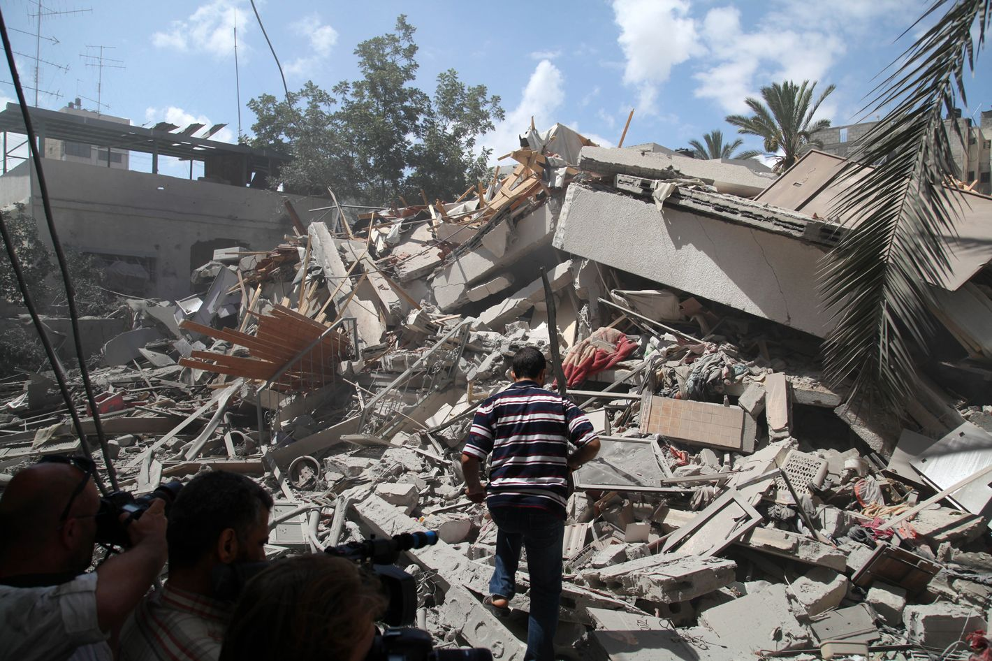 Palestinians look around a house which police said was targeted in Israeli air strikes in Gaza City.