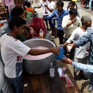 Indian volunteers distribute free cold sweet water on a street in New Delhi.