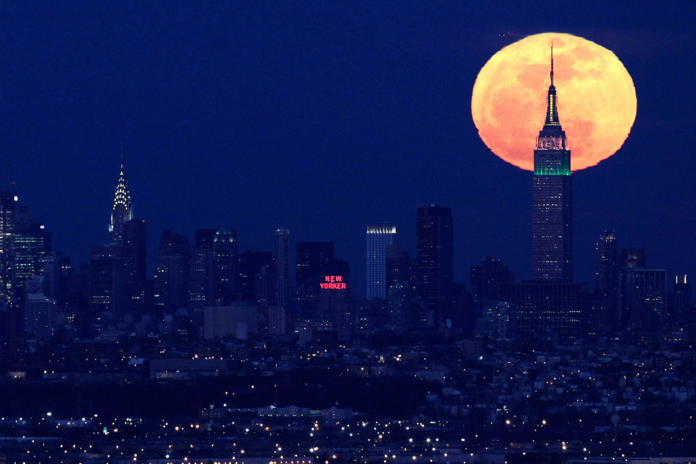 """A full moon rises behind the Empire State Building in New York in this view from Eagle Rock Reservation in West Orange, N.J., in this April 6, 2012 file photo. The biggest and brightest full moon of the year arrives Saturday night May 5, 2012 as our celestial neighbor passes closer to Earth than usual. Saturday's event is a """"supermoon,"""" the closest and therefore the biggest and brightest full moon of the year. At 11:34 p.m., the moon will be about 221,802 miles from Earth. That's about 15,300 miles closer than average. (AP Photo/Julio Cortez, File)"""