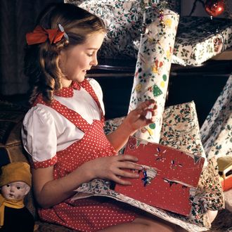 Girl with presents underneath Christmas tree.