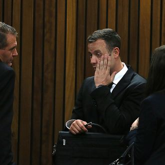 Oscar Pistorius (C) gestures upon his arrival at the court on the third day of his trial at the North Gauteng High Court in Pretoria, on March 5, 2014. Oscar Pistorius's defence sought to prove that a married couple who heard screams on the night of Reeva Steenkamp's death colluded in their testimony, hoping to discredit key witnesses on Wednesday.