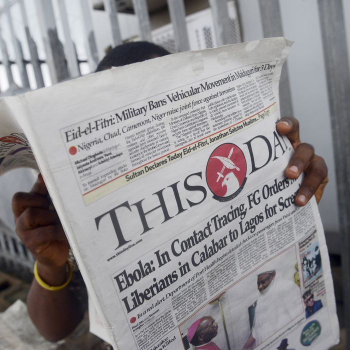 A man reads a newspaper with a headline announcing government efforts to screen for Ebola at a newsstand in Lagos on July 27, 2014. Nigeria was on alert against the possible spread of Ebola on July 27, a day after the first confirmed death from the virus in Lagos, Africa's biggest city and the country's financial capital. The health ministry said on July 25 that a 40-year-old Liberian man died at a private hospital in Lagos from the disease, which has now killed more than 650 people in four west African countries since January. AFP PHOTO/PIUS UTOMI EKPEI (Photo credit should read PIUS UTOMI EKPEI/AFP/Getty Images)