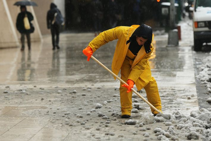 A man clears snow and ice from a sidewalk  along Manhattan's streets on February 2, 2015 in New York City. Another winter storm has brought inclement weather to much of the Northeast, canceling schools and hundreds of flights throughout the New York metro area.