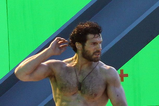 A shirtless Henry Cavill helps the