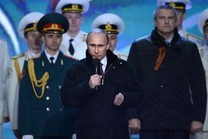 Russia's President Vladimir Putin (C) speaks during a rally to celebrate the incorporation of Crimea at the Red Square in Moscow, on March 18, 2014, with Crimean Prime Minister Sergei Aksyonov (R) attending the rally. Putin pushed today every emotional button of the collective Russian psyche as he justified the incorporation of Crimea, citing everything from ancient history to Russia's demand for respect to Western double standards.