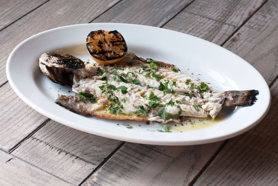 Grilled whole fish lavraki with lemon, extra-virgin olive oil, sea salt, cracked pepper, and herbs.