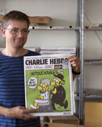 French satirical weekly Charlie Hebdo's publisher, known only as Charb, presents to journalists, on September 19, 2012 in Paris, at the headquarters, the last issue which features on the front cover a satirical drawing titled