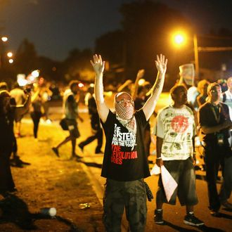 FERGUSON, MO - AUGUST 13: Demonstrators protest the shooting death of teenager Michael Brown on August 13, 2014 in Ferguson, Missouri. Brown was shot and killed by a Ferguson police officer on Saturday. Ferguson, a St. Louis suburb, is experiencing its fourth day of violent protests since the killing. (Photo by Scott Olson/Getty Images)