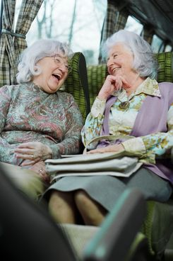 Mature women sitting side by side in coach, laughing