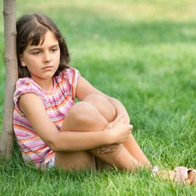 A pretty sad girl in pink is sitting on the summer grass