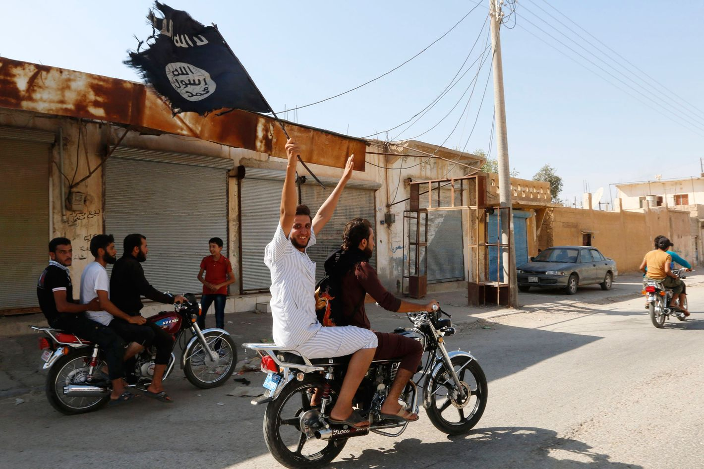 A resident of Tabqa city touring the streets on a motorcycle waves an Islamist flag in celebration after Islamic State militants took over Tabqa air base, in nearby Raqqa city August 24, 2014. Islamic State militants stormed the air base in northeast Syria on Sunday, capturing most of it from government forces after days of fighting over the strategic location, a witness and a monitoring group said. Fighting raged inside the walls of the Tabqa air base, the Syrian army's last foothold in an area otherwise controlled by IS, which has seized large areas of Syria and Iraq. REUTERS/Stringer   (SYRIA - Tags: POLITICS CIVIL UNREST CONFLICT TPX IMAGES OF THE DAY) - RTR43J48