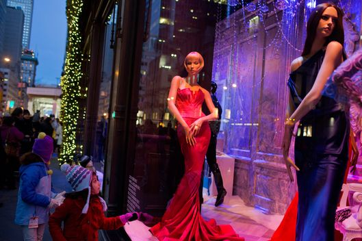 A young girl looks at mannequins in long gowns inside a Saks Fifth Avenue holiday window display in New York, U.S., on Sunday, Dec. 23, 2012. Holiday shoppers descended on U.S. stores this weekend in a last-minute dash to buy gifts amid concerns about the nation?s economy and the impasse in Washington over taxes and spending.