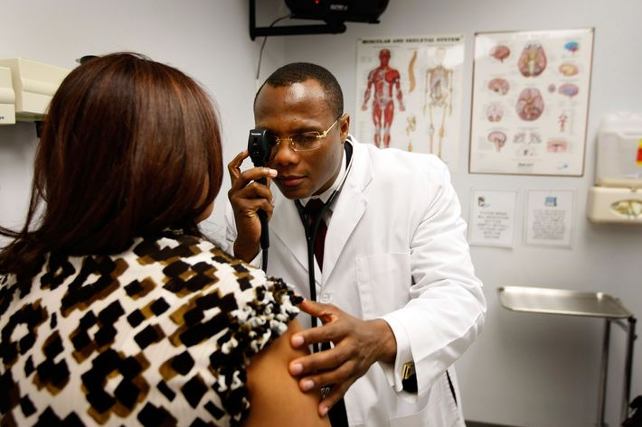 POMPANO BEACH, FL - APRIL 20:  Emlyn Louis, MD speaks with Julia Herrera as he examines her at the Broward Community & Family Health Center on April 20, 2009 in Pompano Beach, Florida.  Mr. Louis's job was saved when the American Recovery and Reinvestment Act provided funds for community health centers.  The Broward Community & Family Health Centers received nearly $1.5 million in Recovery Act funds, allowing them to halt layoffs and instead hire 13 additional employees.  In total, the funds will provide services for an additional 6,600 underserved South Floridians while saving or creating 15 local jobs.  (Photo by Joe Raedle/Getty Images) *** Local Caption *** Emlyn Louis;Julia Herrera