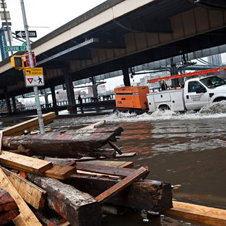NEW YORK, NY - OCTOBER 30: A truck drives through a flooded street, caused by Hurricane Sandy, on October 30, 2012, in the Lower East Side of New York City. The storm has claimed at least 16 lives in the United States, and has caused massive flooding accross much of the Atlantic seaboard. US President Barack Obama has declared the situation a 'major disaster' for large areas of the US East Coast including New York City. (Photo by Andrew Burton/Getty Images)