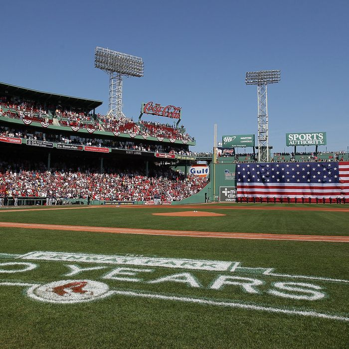 The flag covers the Green Monster as the national anthem is played before the game between the Boston Red Sox and the Tampa Bay Rays on April 16, 2012 at Fenway Park in Boston, Massachusetts.