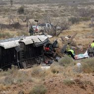 Officials investigate the scene of a prison transport bus crash in Penwell, Texas, Wednesday, Jan. 14, 2015. Law enforcement officials said the bus carrying prisoners and corrections officers fell from an overpass in West Texas and crashed onto train tracks below, killing at least 10 people. (AP Photo/The Odessa American, Mark Sterkel)