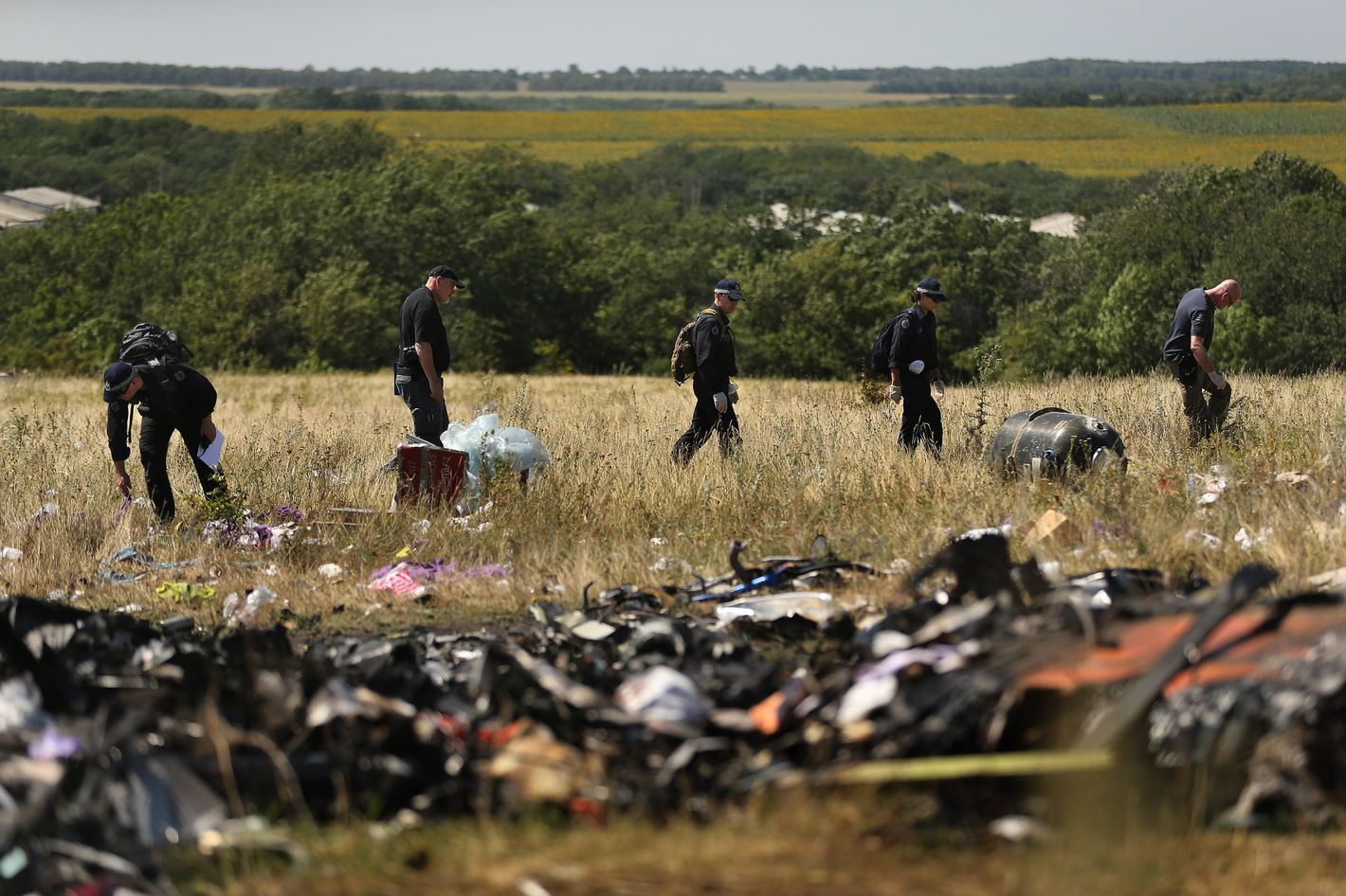 Australian Federal Police officers and their Dutch counterparts collect human remains and personal belongings from the MH17 Malaysian Airlines crash site in the fields outside the village of Grabovka, Eastern Ukraine, August 1, 2014. This is the first time a full forensic party searches the site.  (Photo by Kate Geraghty/The Sydney Morning Herald/Fairfax Media via Getty Images).