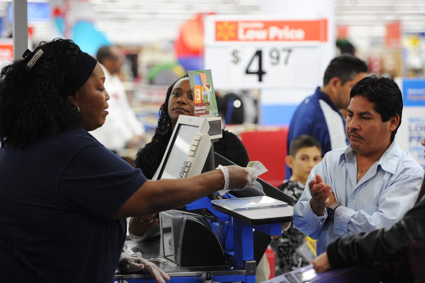 """An employee rings up sales at a cash register at a  Walmart in the Crenshaw district of Los Angeles on Black Friday, November 29, 2013. US stocks Friday moved higher in a holiday-shortened session following better eurozone economic data and positive early assessments of """"Black Friday"""" shopping traffic by some leading retailers.    AFP PHOTO / Robyn Beck        (Photo credit should read ROBYN BECK/AFP/Getty Images)"""