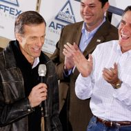 Sen John Thune (R-SD) (L) gets a laugh and applause from former Massachusetts Gov. and Republican presidential candidate Mitt Romney (R) and Rep. Jason Chaffetz (R-UT) during a rally at the Weber Paper Company January 2, 2012 in Dubuque, Iowa.