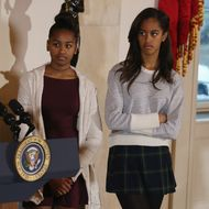 """WASHINGTON, DC - NOVEMBER 26:  Malia (R) and Sasha Obama listen to their father U.S. President Barack Obama speak before pardoning """"Cheese"""" and his alternate Mac both, 20-week old 48-pound during a ceremony at  the White House November 26, 2014 in Washington, DC. The Presidential pardon of a turkey has been a long time Thanksgiving tradition that dates back to the Harry Truman administration.(Photo by Mark Wilson/Getty Images)"""