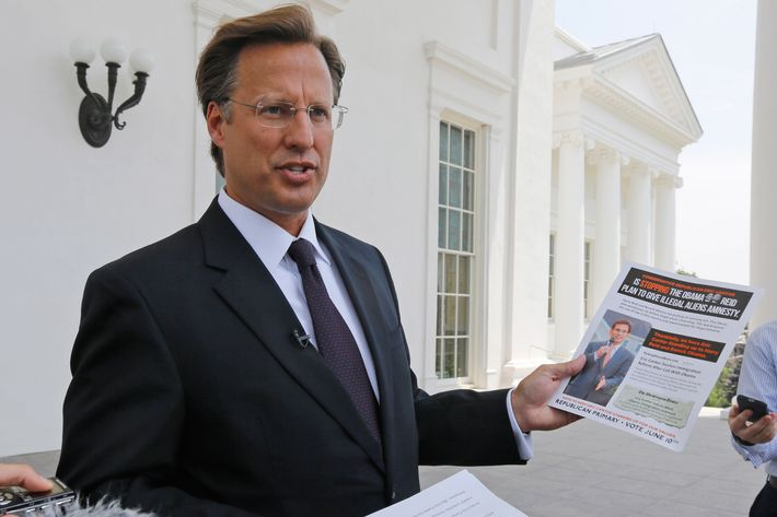 Seventh District US Congressional Republican candidate, David Brat displays an immigration mailer by Congressman Eric Cantor during a press conference at the Capitol in Richmond, Va., Wednesday, May 28, 2014. Brat challenged Congressman Eric Cantor's stand on immigration, claiming that Cantor backs amnesty. Cantor is getting pressured from both sides over immigration as his Republican primary election nears and the window for legislative action narrows. (AP Photo/Steve Helber)