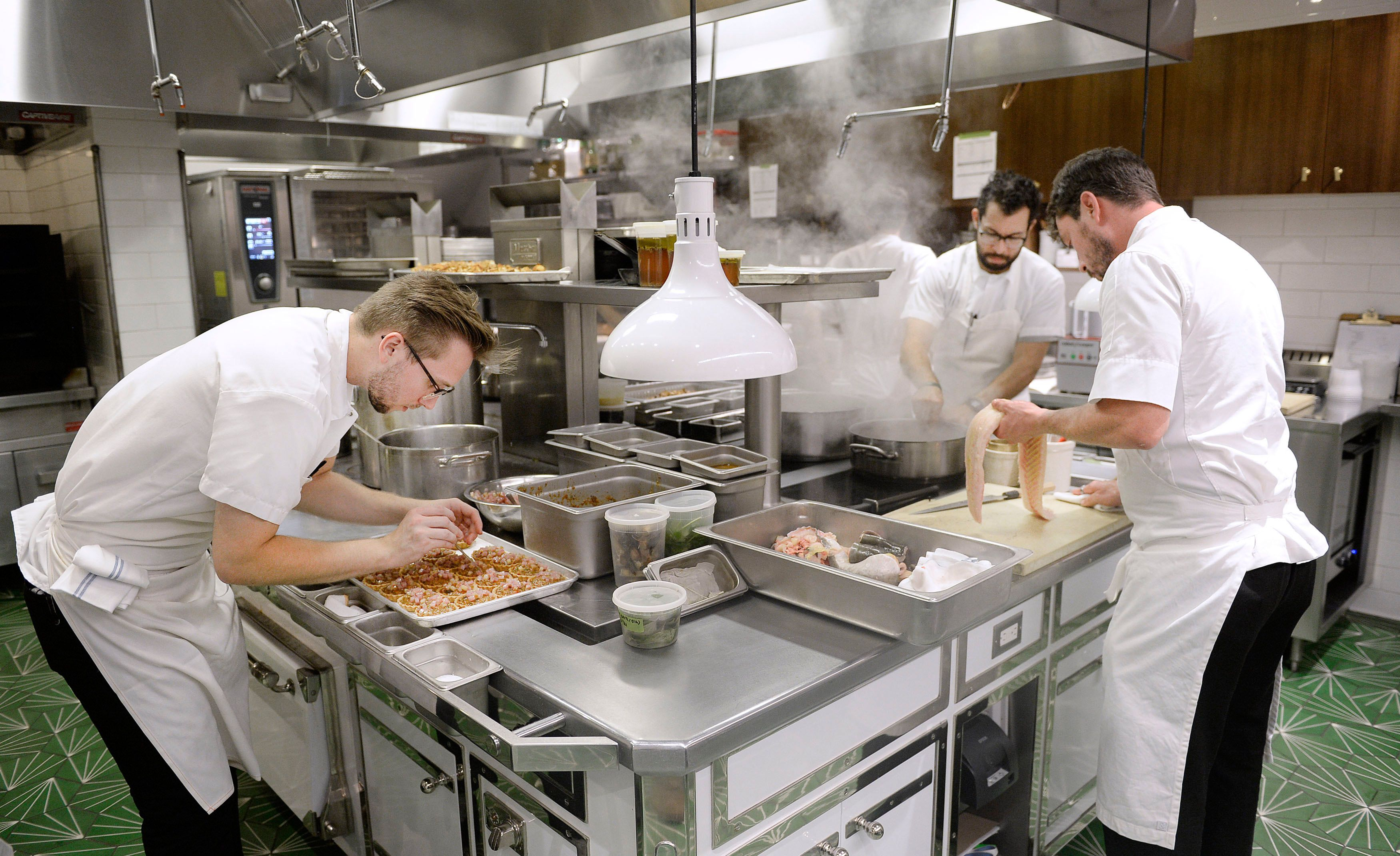 Kitchen staffers prepare dishes at Pineapple And Pearls restaurants on September 21, 2016, in Washington, DC.