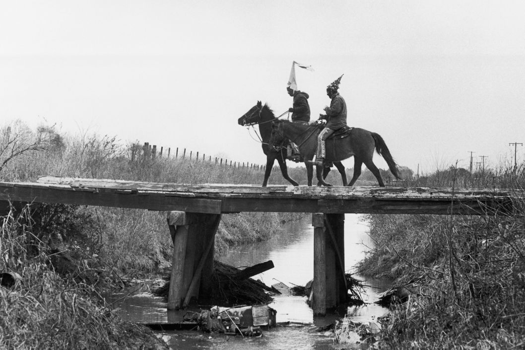 ca. 1978, Mamou, Louisiana, USA --- Two costumed Cajun Mardi Gras riders cross a bridge. Mamou, Louisiana. --- Image by ? Philip Gould/Corbis