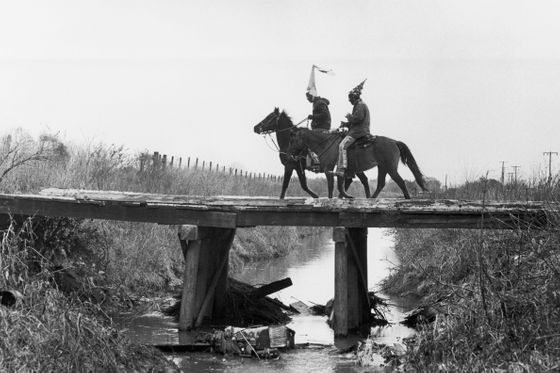 ca. 1978, Mamou, Louisiana, USA --- Two costumed Cajun Mardi Gras riders cross a bridge. Mamou, Louisiana. --- Image by © Philip Gould/Corbis