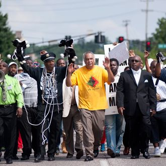 Protesters fill Florissant Road in downtown Ferguson, Mo. Monday, Aug. 11, 2014, marching along the closed street. The rally marched along the street in front of the town's police headquarters to protest the shooting of 18-year-old Michael Brown by Ferguson police officers on Saturday. (AP Photo/Sid Hastings)