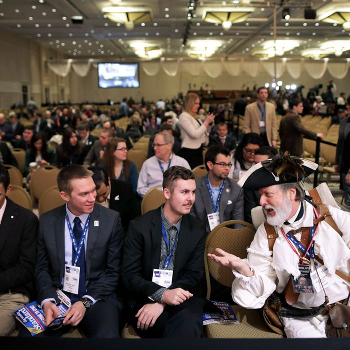 Dressed in American revolutionary clothing, William Temple (R) of Brunswick, Georgia visits with students (L-R) Nicholas Blincoe, Matthew Leahy and Elliot Brietta of Scottsdale, AZ, during the second day of the Conservative Political Action Conference at the Gaylord International Hotel and Conference Center March 7, 2014 in National Harbor, Maryland. The CPAC annual meeting brings together conservative politicians, pundits and their supporters for speeches, panels and classes.