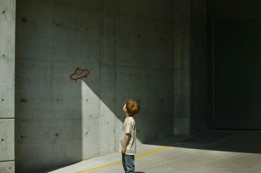Boy (4-6) looking at graffiti UFO with beam of light