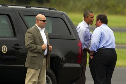 US President Barack Obama (C) speaks with New Jersey Governor Chris Christie (R) as he prepares to depart Paterson, New Jersey, September 4, 2011, after touring the devastation left by Hurricane Irene.