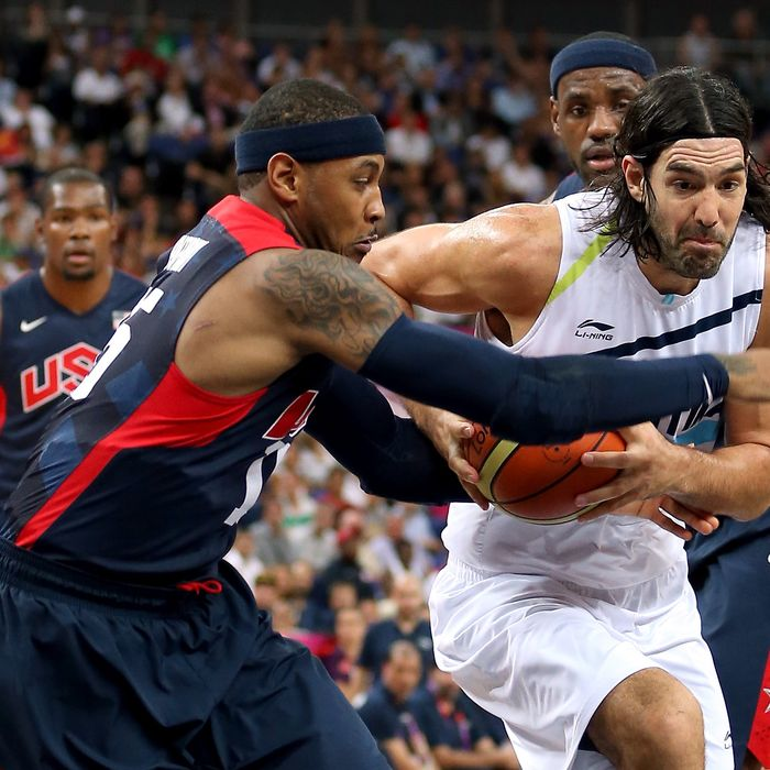 Luis Scola #4 of Argentina drives between Carmelo Anthony #15 and LeBron James #6 of United States in the first half during the Men's Basketball semifinal match on Day 14 of the London 2012 Olympic Games at the Basketball Arena on August 10, 2012 in London, England.