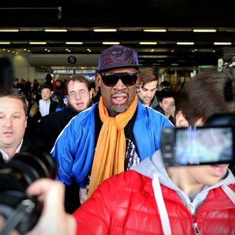 Former US basketball player Dennis Rodman (C) is surrounded by the media as he arrives at Beijing International Airport from North Korea on January 13, 2014. Rodman returned to China from Pyongyang after a seven-day trip where he sang