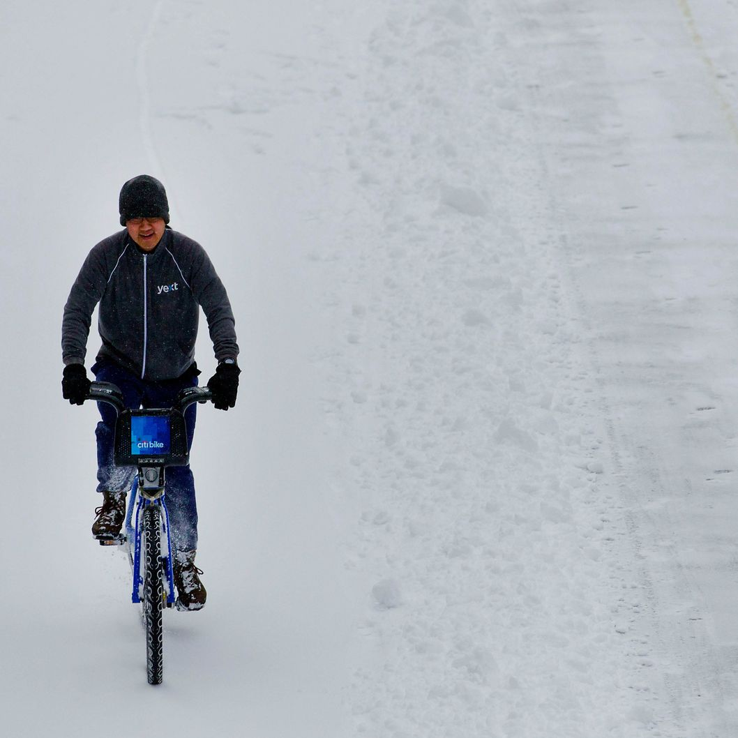 A bicyclist rides a Citi Bike through the snow in New York, U.S., on Friday, Jan. 3, 2014.