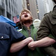 NEW YORK, NY - NOVEMBER 17:  Protesters affiliated with the Occupy Wall Street movement lock arms at the intersection of  Exchange Place and Beaver Street in the Financial District on November 17, 2011 in New York City. Protesters attempted to shut down the New York Stock Exchange today, blocking roads and tying up traffic in Lower Manhattan.  (Photo by Andrew Burton/Getty Images)