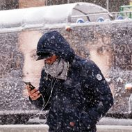 A man uses his smartphone as he crosses a street during a winter storm in New York on March 5, 2015. An airplane skidded of the runway Thursday at New York's La Guardia airport and hit a fence, officials said, as heavy snow fell in the city. Forecasters had warned of low visibility as a major storm hits the region. AFP PHOTO/JEWEL SAMAD (Photo credit should read JEWEL SAMAD/AFP/Getty Images)