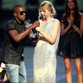 Kayne West (L)jumps onstage after Taylor Swift (C) won the