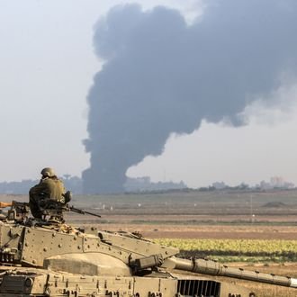 Israeli soldiers sitting on a tank hold their position on the Israeli side of the border with the Gaza Strip, on July 22 , 2014, as smoke billows from the coastal Palestinian enclave following an Israeli army ground operation to destroy tunnels reportedly used by Palestinian militants from the Gaza Strip to enter Israel. The UN chief and Washington's top diplomat are holding a flurry of meetings in Cairo to push for an end to two weeks of violence in Gaza that has killed sp far 585 Palestinians. AFP PHOTO / JACK GUEZ (Photo credit should read JACK GUEZ/AFP/Getty Images)