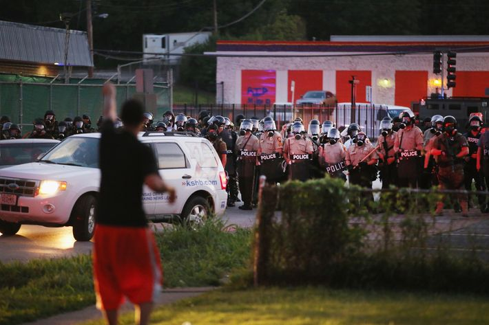 FERGUSON, MO - AUGUST 11: Police force protestors from the business district into nearby neighborhoods on August 11, 2014 in Ferguson, Missouri. Police responded with tear gas and rubber bullets as residents and their supporters protested the shooting by police of an unarmed black teenager named Michael Brown who was killed Saturday in this suburban St. Louis community. Yesterday 32 arrests were made after protests turned into rioting and looting in Ferguson. (Photo by Scott Olson/Getty Images)