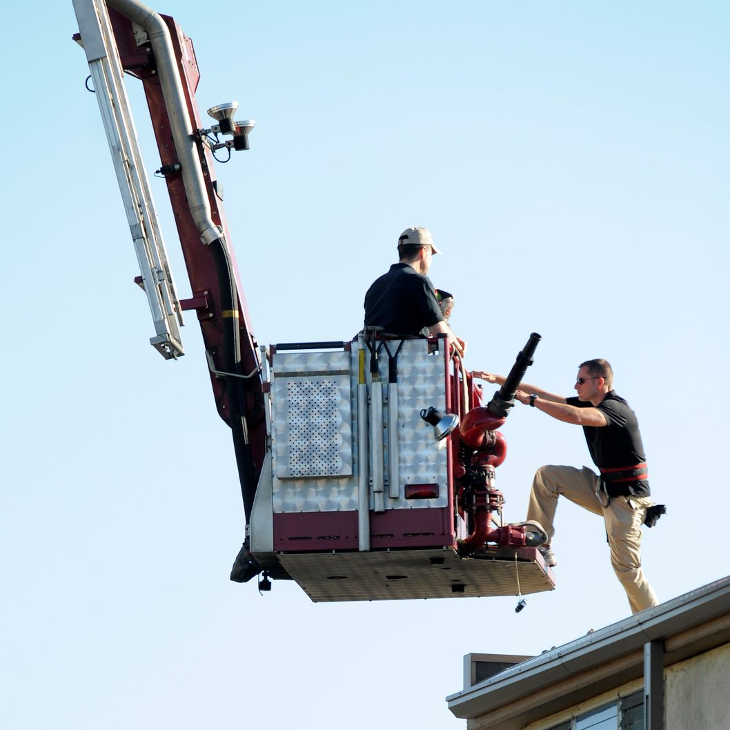 AURORA, CO - JULY 21:  A law enforcement official climbs onto the roof of an adjacent building as they prepare to disarm the booby-trapped apartment of suspect James Holmes after he went on a shooting rampage at nearby Century 16 movie theatre during an early morning screening of the new Batman movie, 'The Dark Knight Rises'  on July 21, 2012 in Aurora, outside of Denver, Colorado. According to reports, 12 people have been killed and over 59 injured. Police have the suspect, twenty-four year old James Holmes of North Aurora, in custody and are now dealing with various devices and trip wires in the apartment. (Photo by Chris Schneider/Getty Images)  