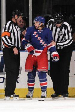 NEW YORK, NY - DECEMBER 13: Referee Don Van Massenhoven #21 and linesman Mike Cvik #88 escort Carl Hagelin #62 of the New York Rangers to the penalty box after his first period charging penalty against the Dallas Stars  at Madison Square Garden on December 13, 2011 in New York City.  (Photo by Bruce Bennett/Getty Images)