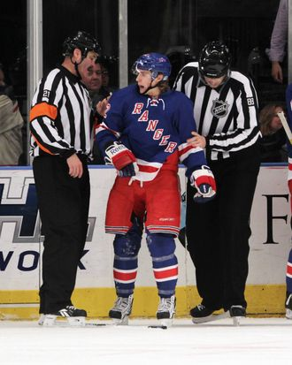 Referee Don Van Massenhoven #21 and linesman Mike Cvik #88 escort Carl Hagelin #62 of the New York Rangers to the penalty box after his first period charging penalty against the Dallas Stars at Madison Square Garden on December 13, 2011.