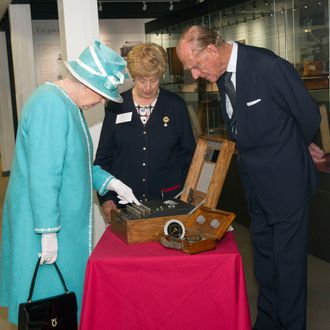 MILTON KEYNES, UNITED KINGDOM - JULY 15: Queen Elizabeth II presses the button to start the enigma code breaking machine as Prince Philip, Duke of Edinburgh and wartime operator Ruth Bourne look on during a visit to Bletchley Park on July 15, 2011 in Milton Keynes, England. Bletchley Park is the historic site of secret British code-breaking activities during WWII. (Photo by Arthur Edwards - WPA Pool/Getty Images)