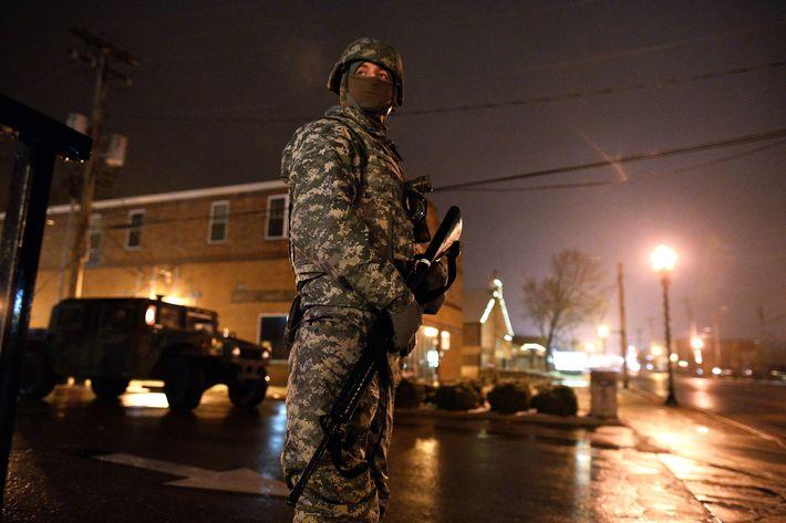 A National Guard trooper keeps vigil on a street near police station in Ferguson, Missouri, on November 26, 2014.