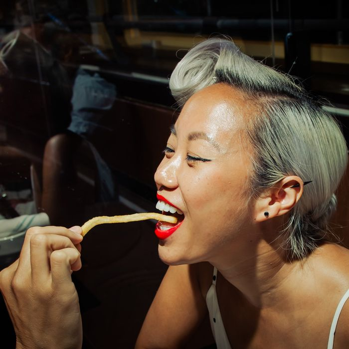 A woman sensually eating a single French fry at the restaurant Pastis
