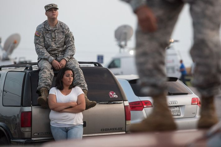 Lucy Hamlin and her husband, Spc. Timothy Hamlin, wait for permission to re-enter the Fort Hood military base, where they live, following a shooting on base on Wednesday, April 2, 2014, in Fort Hood, Texas. One person was killed and 14 injured in the shooting, and officials at the base said the shooter is believed to be dead. The details about the number of people hurt came from two U.S. officials who spoke on condition of anonymity because they were not authorized to discuss the information by name. (AP Photo/ Tamir Kalifa)