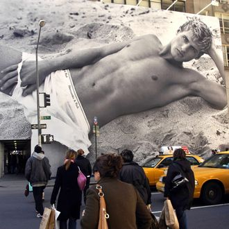 Pedestrians walk by a sexually suggestive billboard on the construction shed of the Abercrombie & Fitch store on Fifth Avenue.