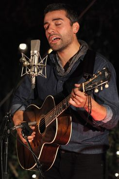 """Actor Oscar Issac performs onstage during reception honoring Joel and Ethan Coen and T Bone Burnett to celebrate the music of """"Inside Llewyn Davis"""" at Buffalo Club on November 13, 2013 in Santa Monica, California."""
